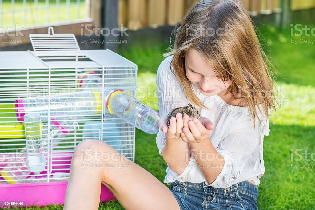 Girl with a hamster in palms stock photo