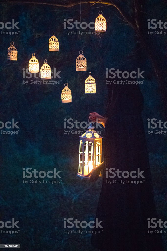 girl with a lantern at night in the forest stock photo