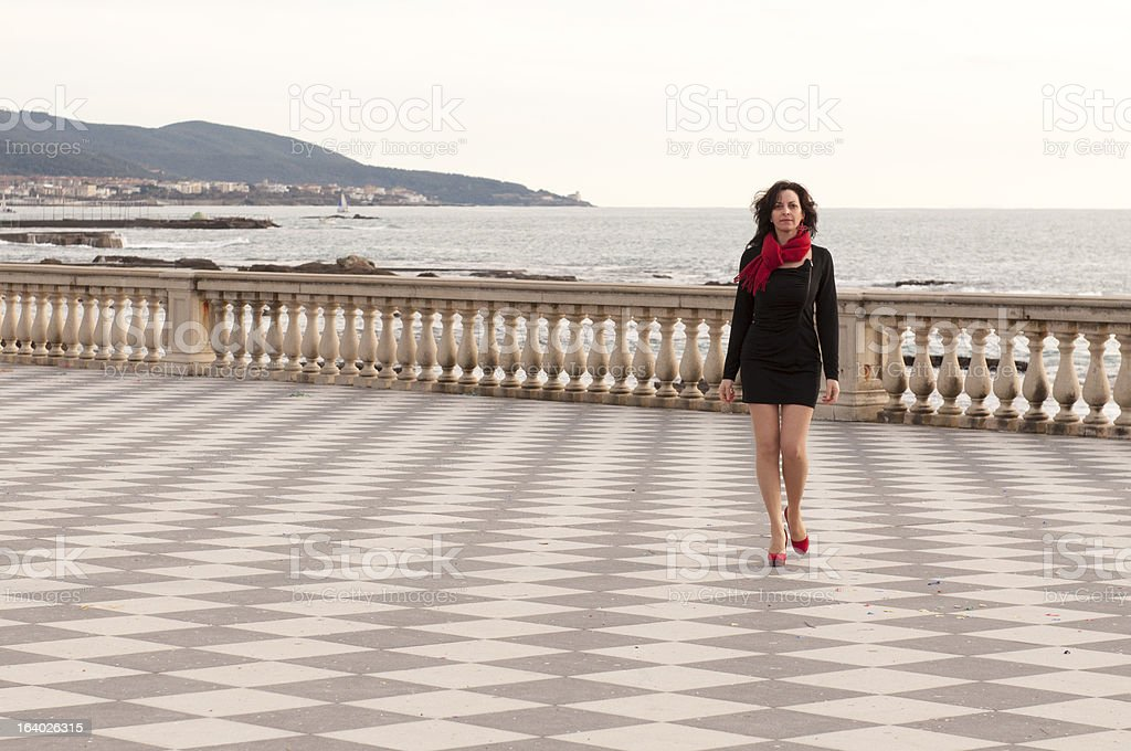 Girl with a little black dress walking on the promenade royalty-free stock photo