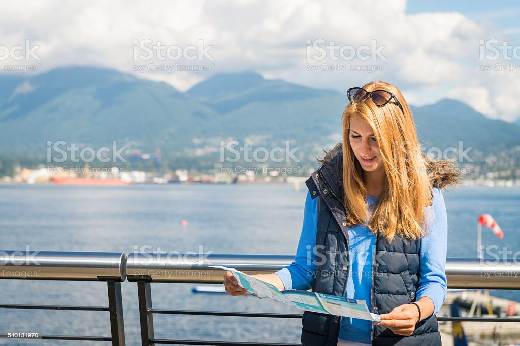 Girl with a map in the city stock photo