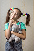 girl with a teddy bear thoughtfully looking up