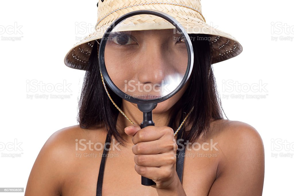Girl with a traveler's hat looks through a magnifying glass stock photo