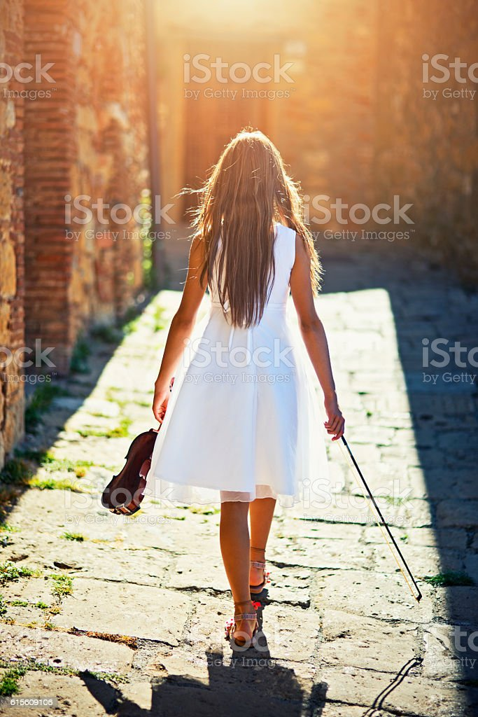 Girl with a violin walking in the sunny street stock photo