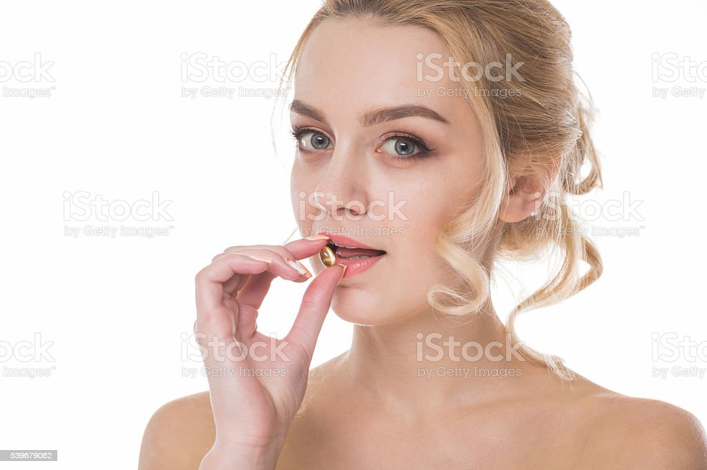 Girl with a yellow pill in hand stock photo