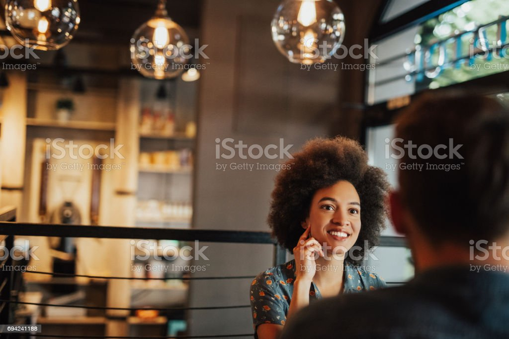 Girl with afro hairstyle looking at the man across the table stock photo