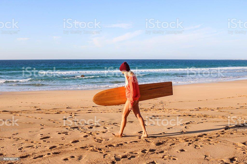 Girl with alaya surfboard walking on the beach stock photo