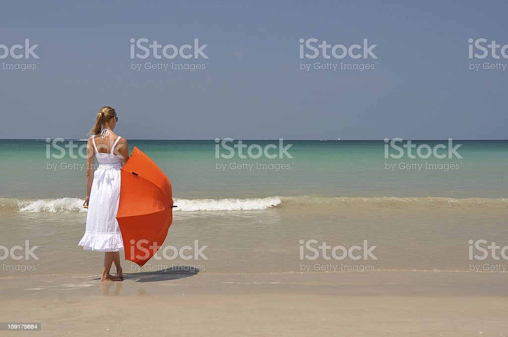 Girl with an orange umbrella on the sandy beach royalty-free stock photo