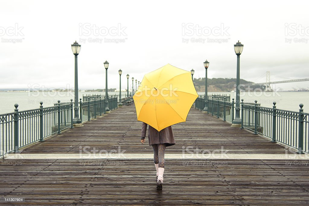 A girl with an umbrella on a San Francisco pier stock photo