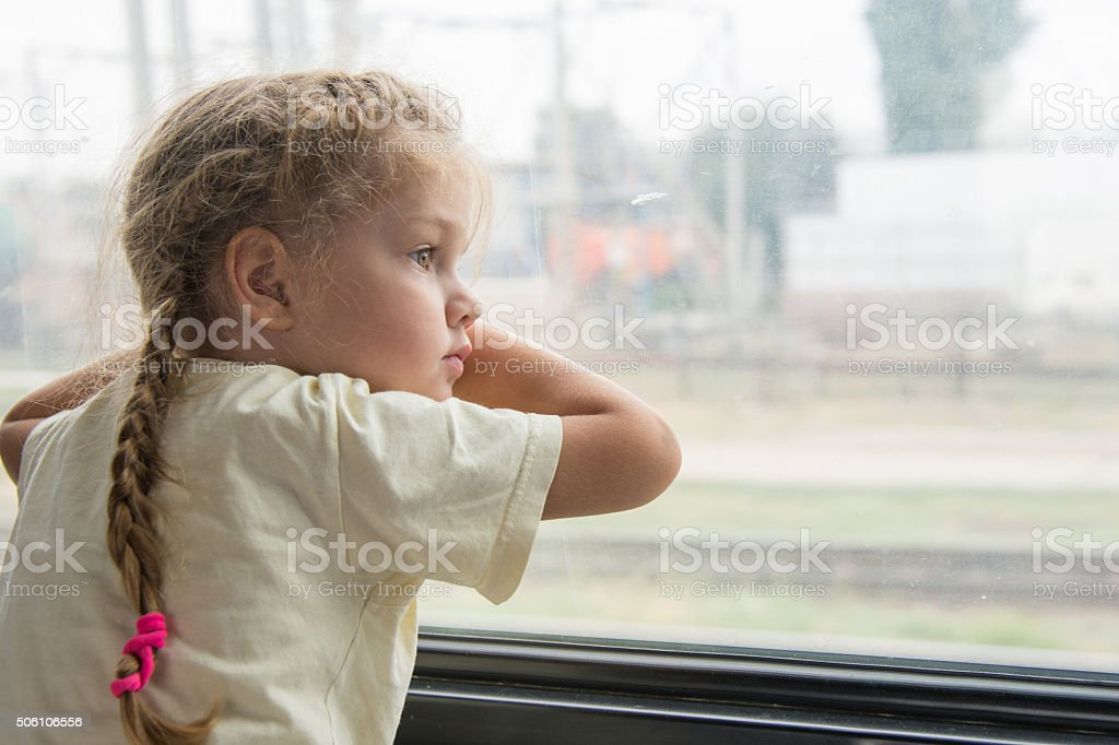 Girl with anxiety sadness looks out window of train car stock photo