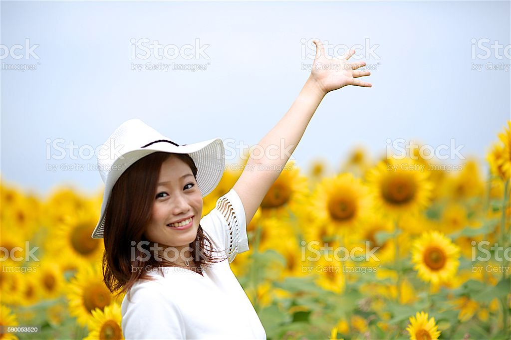 Girl with arm up at sunflower field stock photo