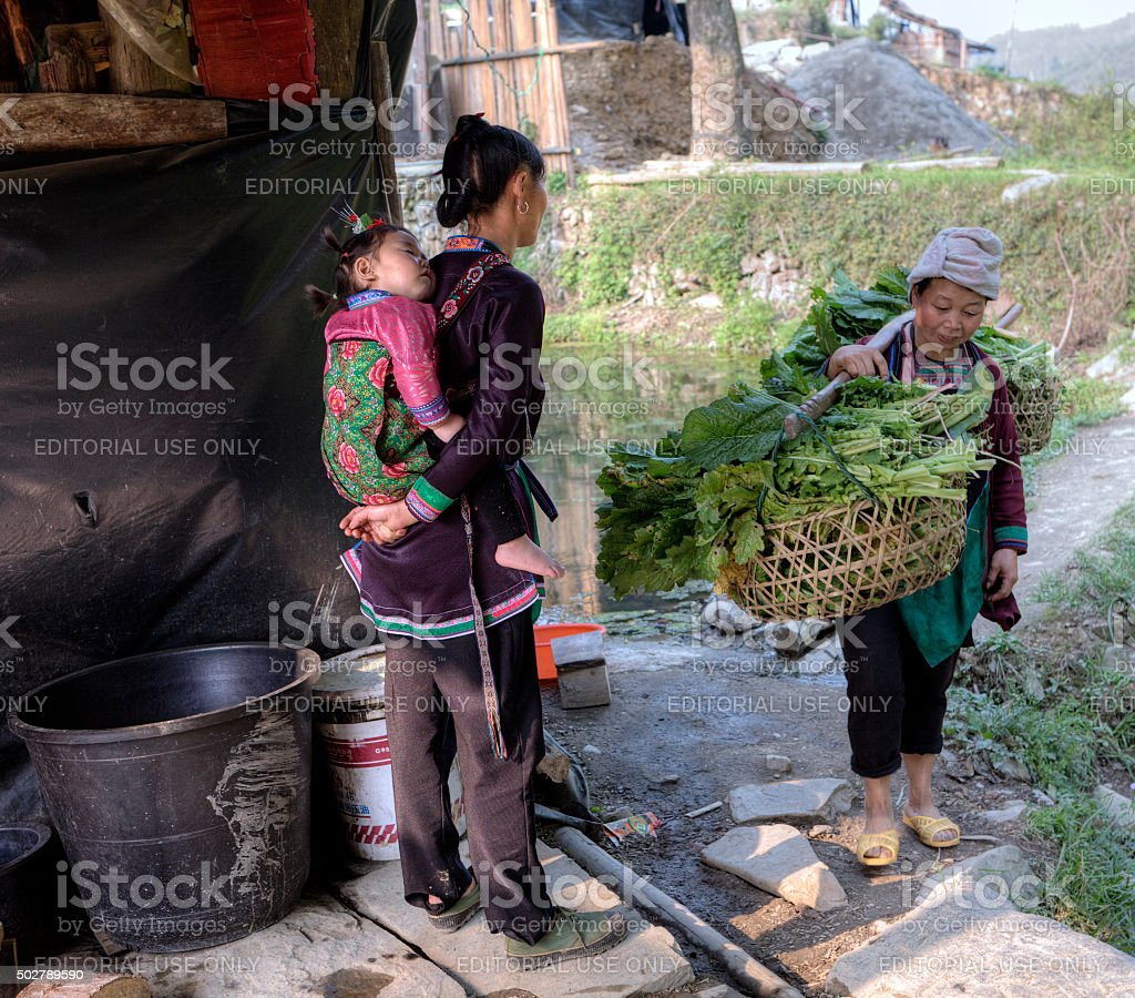 Girl with baby on her back, met woman carrying yoke. stock photo