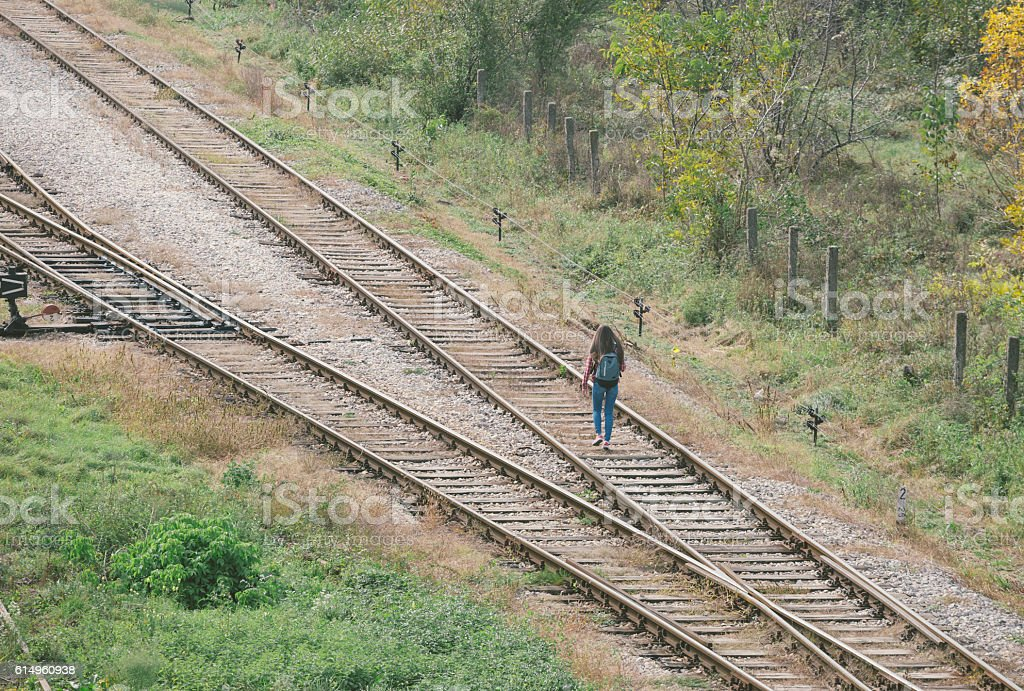 Girl with backpack walking away in distance by railroad track stock photo