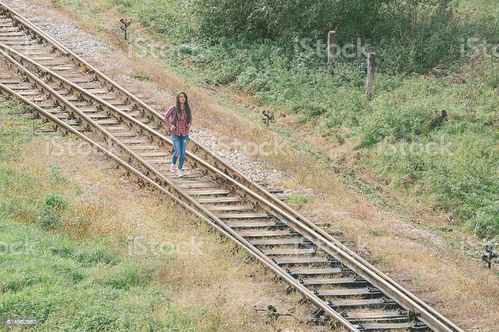 Girl with backpack walking down the railroad track stock photo