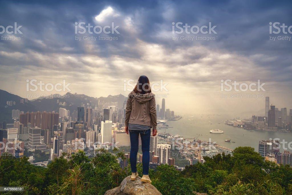 girl with backpacker enjoying sunlight on peak of foggy city. high on the peak of rocks mountain with sunset at Hongkong city . success,winner, leader concept. stock photo
