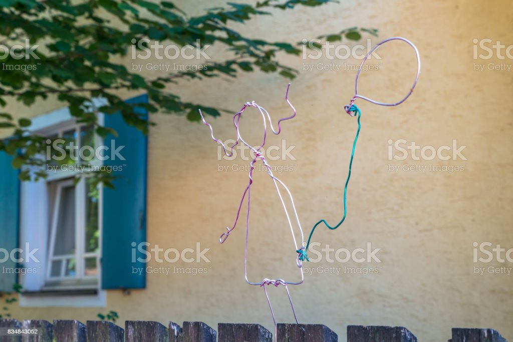 Girl with balloon bent with coloured metal wire stock photo