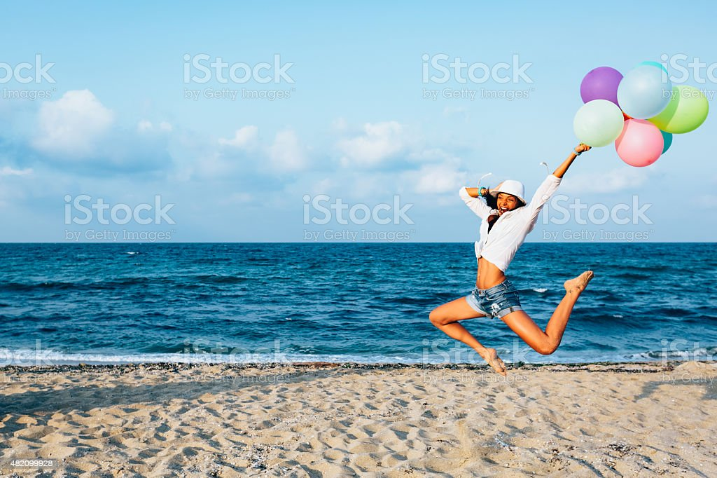 Girl with balloons jumping from joy at the beach stock photo