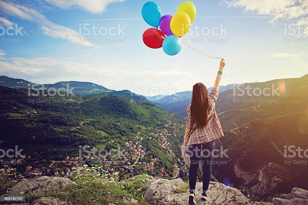 Girl with baloons is standing on the edge stock photo
