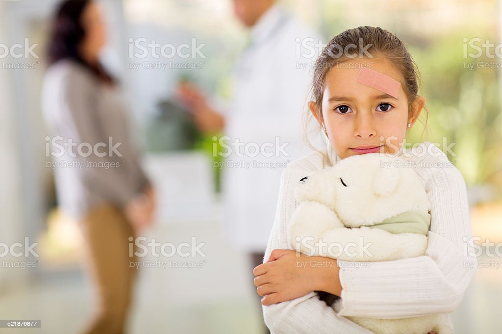 girl with band-aid on her face holding a teddy bear stock photo