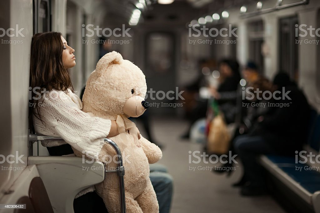 Girl with bear in a subway car. stock photo