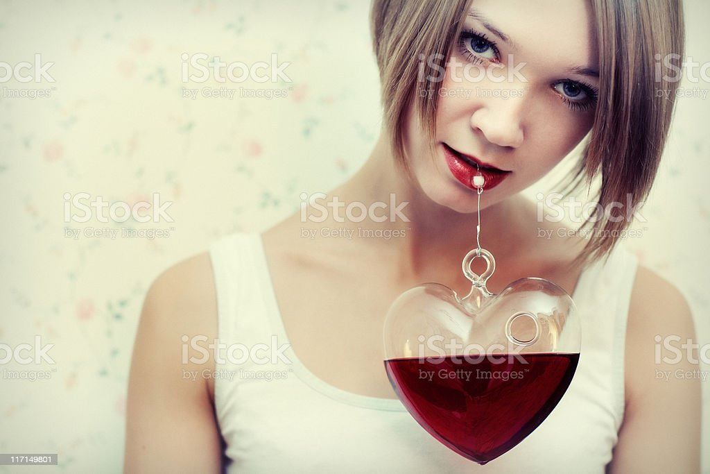 Girl with beautiful eyes keeps mouth glass heart stock photo