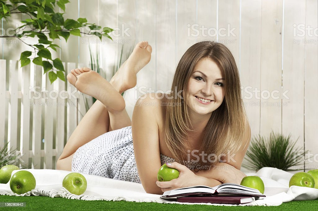 Girl with book and apple in the garden royalty-free stock photo