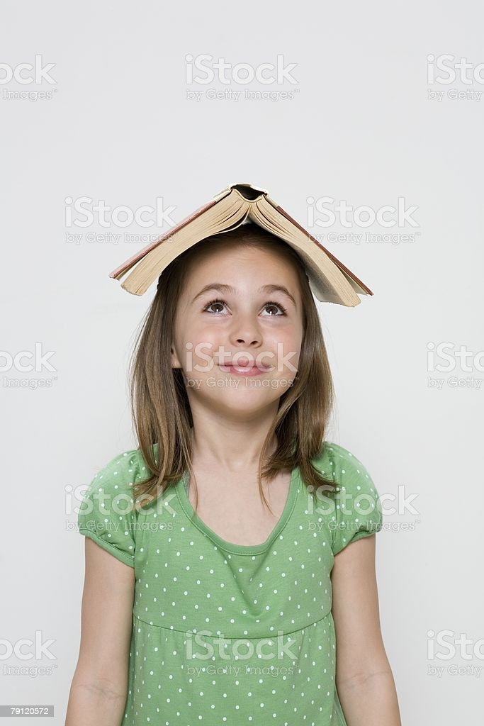 Girl with book on her head royalty-free stock photo