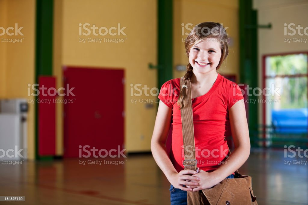 Girl with bookbag standing in school gym stock photo