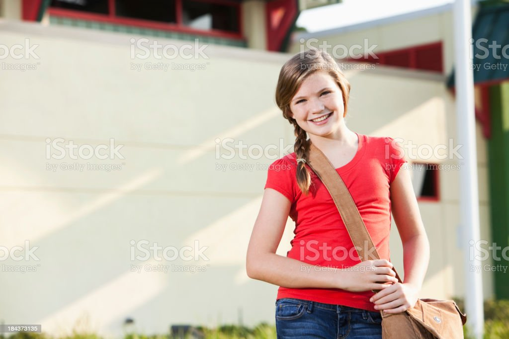 Girl with bookbag standing outside school stock photo