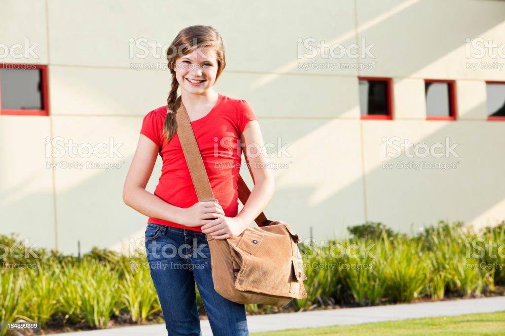 Girl with bookbag standing outside school stock photo