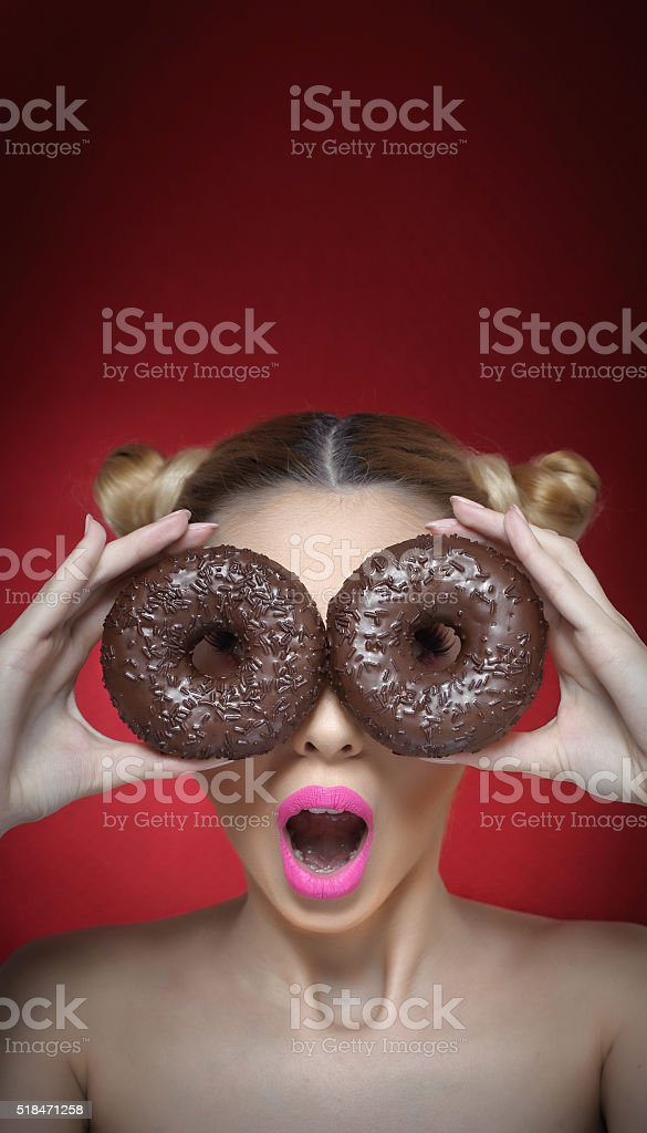 girl with bright pink lipstick holding two chocolate donuts stock photo