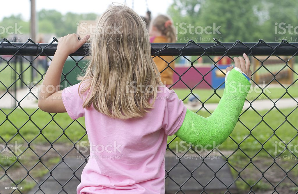 Girl with broken arm wishing she could play at playground. stock photo