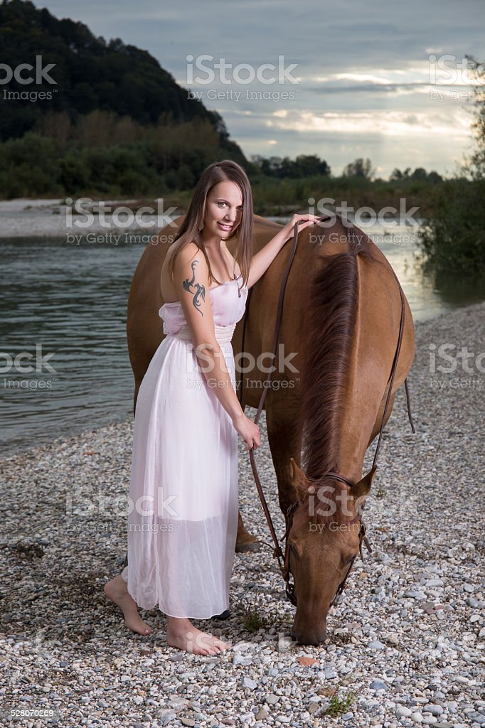 Girl with brown horse by river stock photo