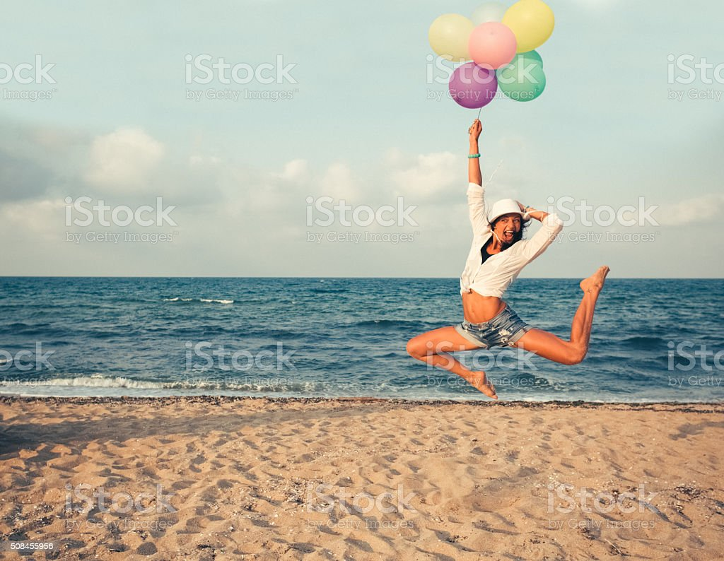 Girl with bunch of balloons jumping at the beach stock photo