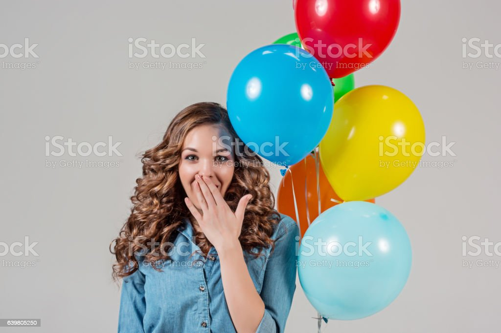 girl with bunch of colorful balloons stock photo