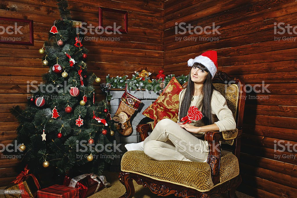 Girl with candy near Christmas tree stock photo
