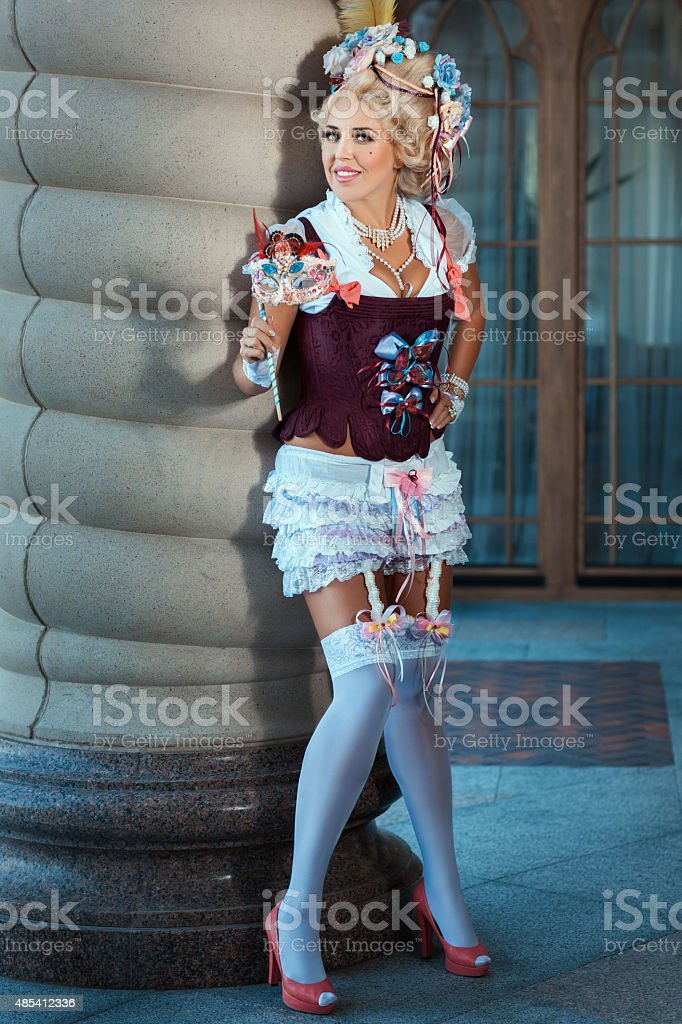 Girl with carnival mask hand and an old vintage dress. stock photo