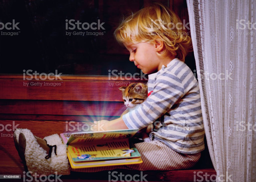 Girl with Cat Looking in a Magic Book stock photo