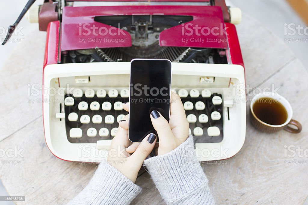 Girl with cell phone and typewriter stock photo