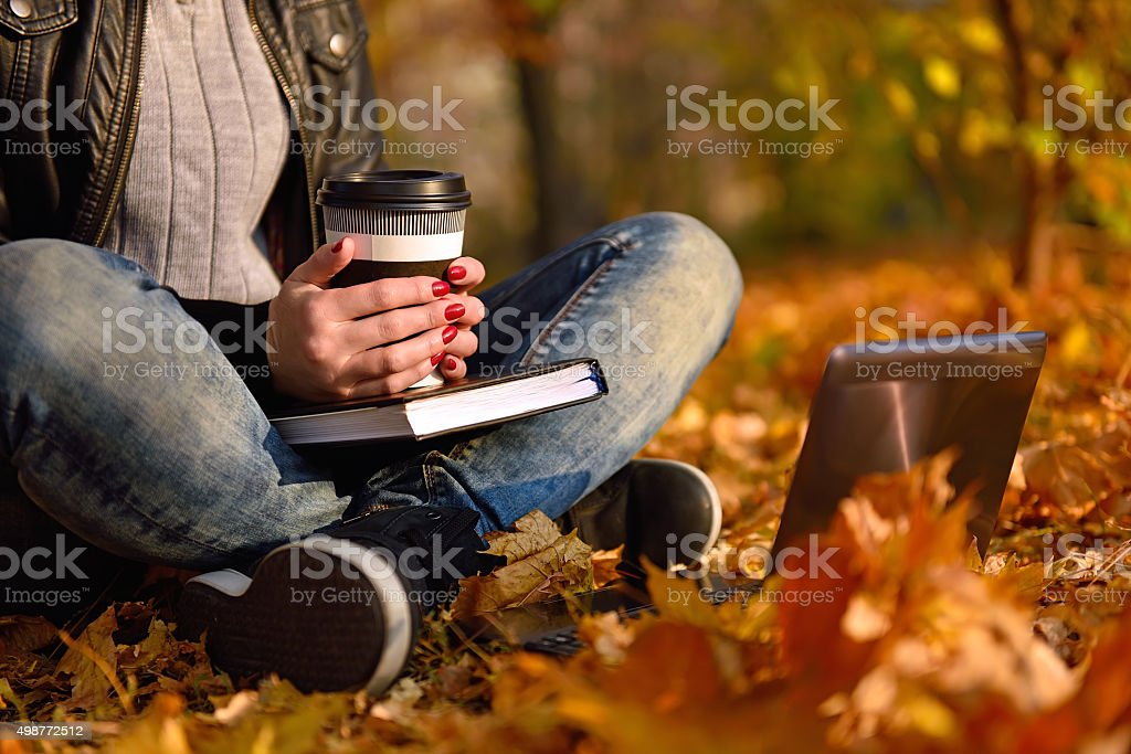 girl with coffee sitting in park stock photo