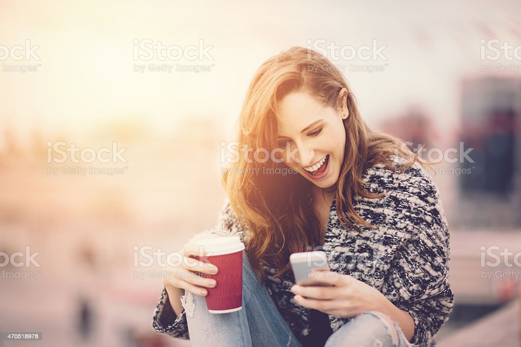 Girl with coffee texting on smartphone stock photo