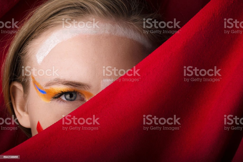 Girl with color make-up on a red background. stock photo