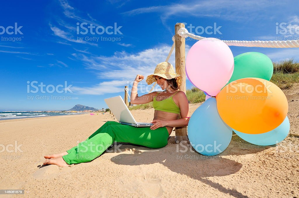 girl with colorful balloons and laptop on the beach royalty-free stock photo