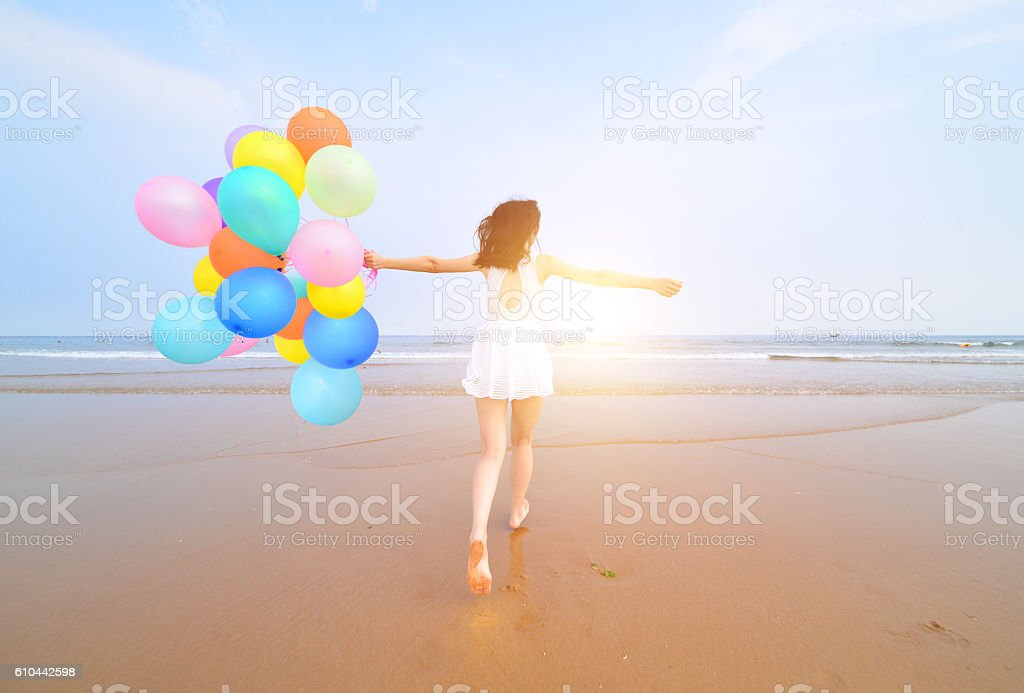 girl with colorful balloons jumping on the beach stock photo
