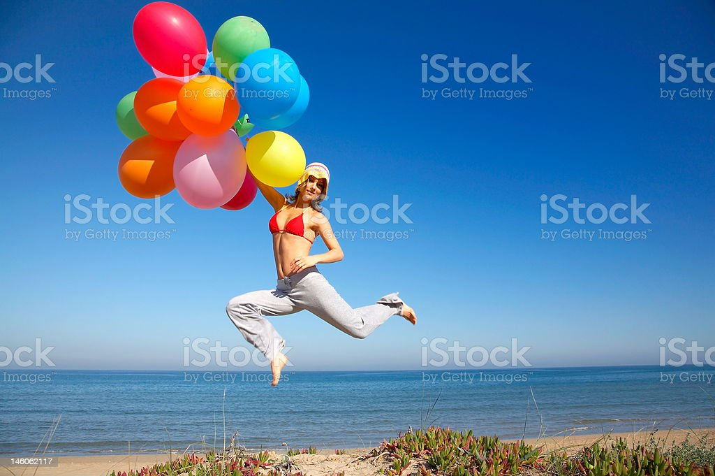 girl with colorful balloons jumping royalty-free stock photo