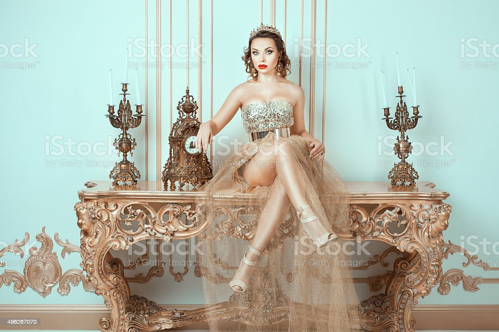 Girl with crown  his head sitting on an old table. stock photo