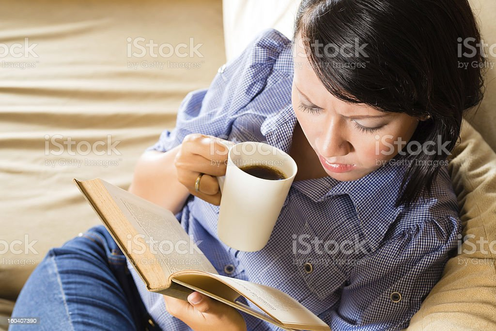 Girl with cup reading Book royalty-free stock photo