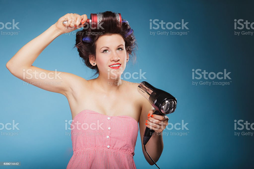 girl with curlers in hair holds hairdreyer stock photo