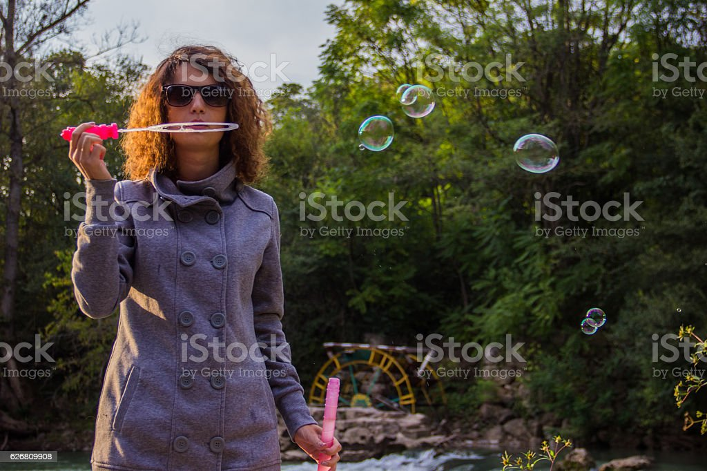 Girl with curles blowing bubbles royalty-free stock photo