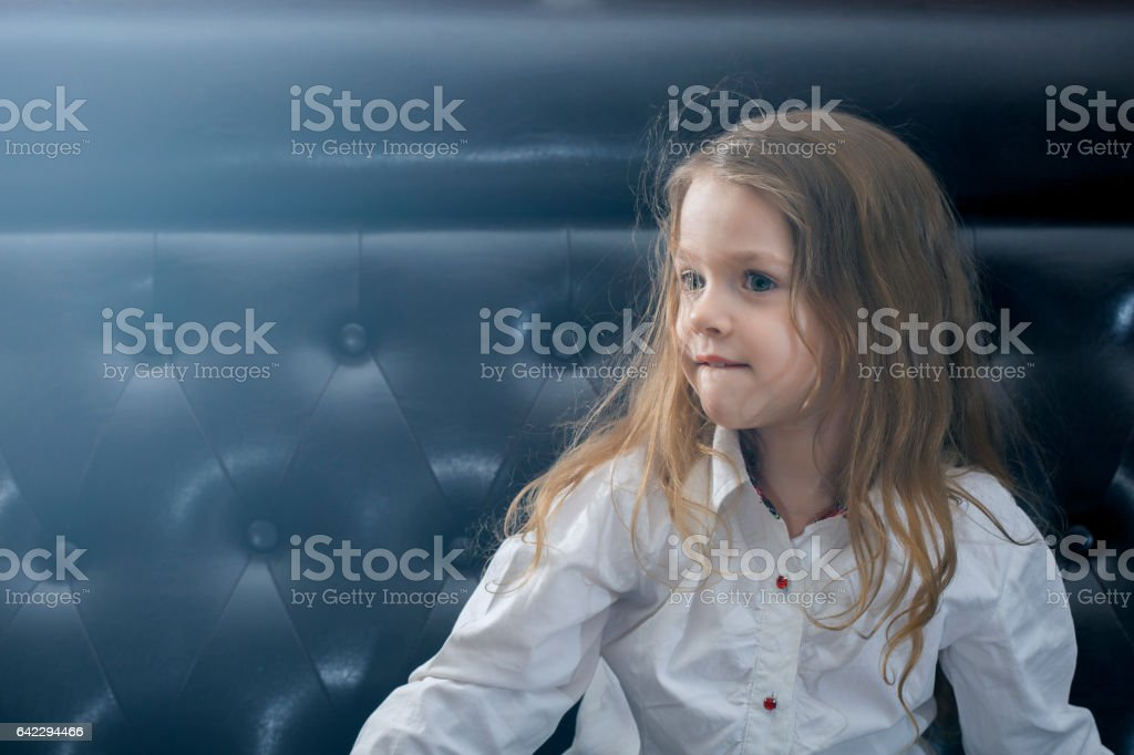 Girl with curly hair sits on couch biting her lip stock photo