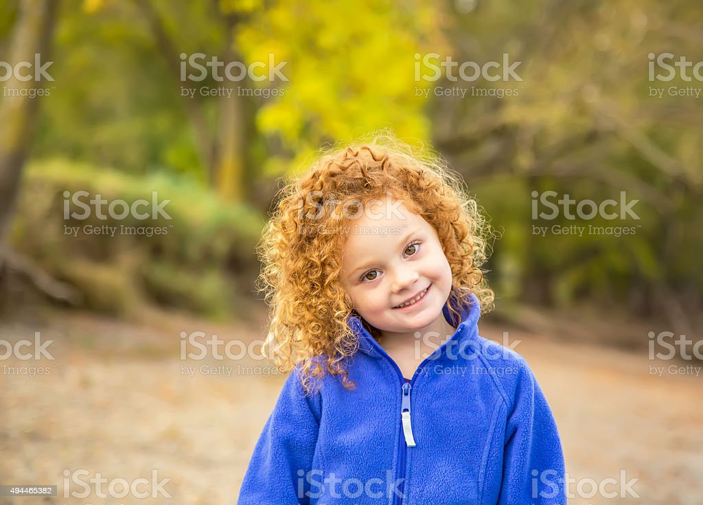 Girl With Curly Red Hair on Riverbank in Autumn stock photo